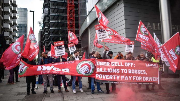 Uber drivers protest outside the Uber offices in London.
