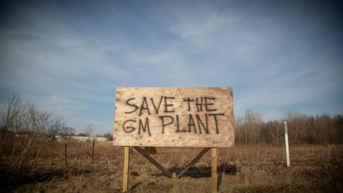 A spray painted billboard sign sits adjacent to the Lordstown GM plant