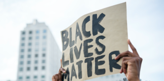 """A protestor holds up a sign reading """"Black Lives Matter"""" during a demonstration in Berlin, on July 10, 2016 with the motto """"Black Lives Matter - No Justice = No Peace"""" as protest over the deaths of two black men at the hands of police last week."""